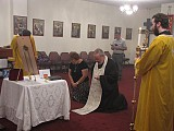 Karlene and Fr. Joseph kneel<br>in prayer before the icon